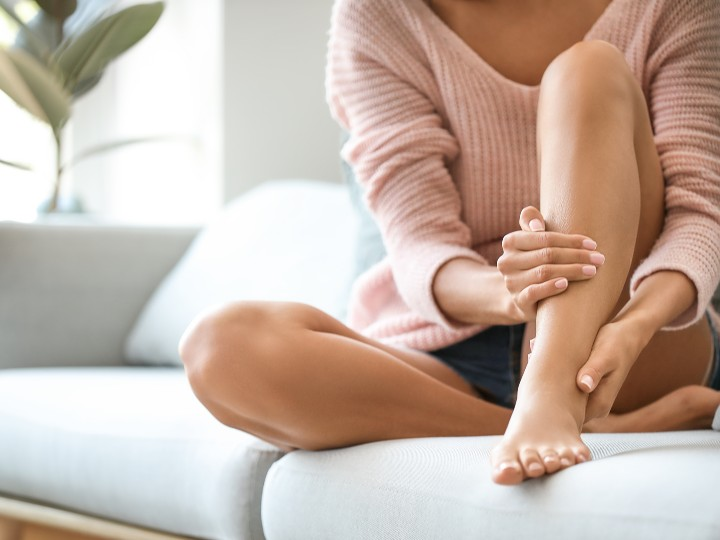 woman holding leg and ankle in pain